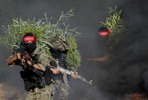 مقاتلون من الجبهة الديموقراطية لتحرير فلسطين خلال مناورات استعراضية في حفل تخرجهم في خان يونس