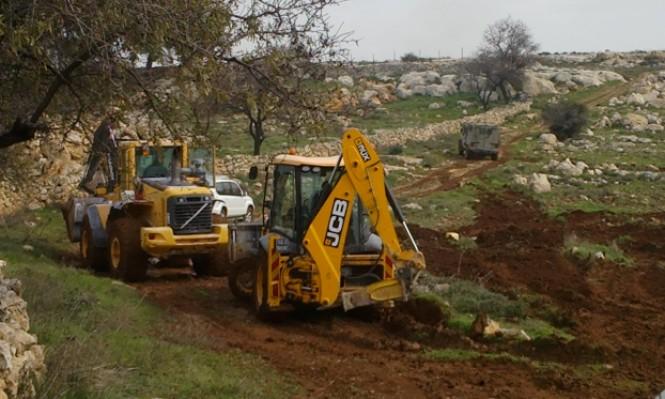 الاحتلال يصادر أراض لشق طريق استيطاني ويخطر بهدم مساكن