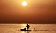 صورة تُظهر صياديْن فلسطينيّيْن في غزة، مع شروق الشمس،