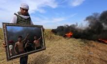شاب فلسطينيّ يحمل مرآة بالقرب من الشريط الحدودي لغزة