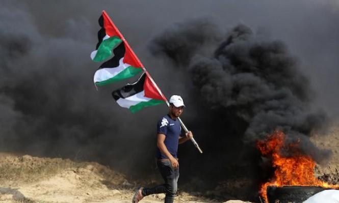 فلسطينيّ غزيّ يرفع الأعلام الفلسطينيّة