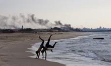 شابان يتدربان على شاطئ غزّة ودخان المظاهرات خلفهما