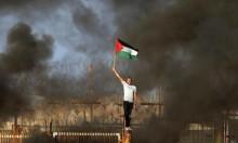 شاب يرفع العلم الفلسطيني على حاجز زيكيم في غزة