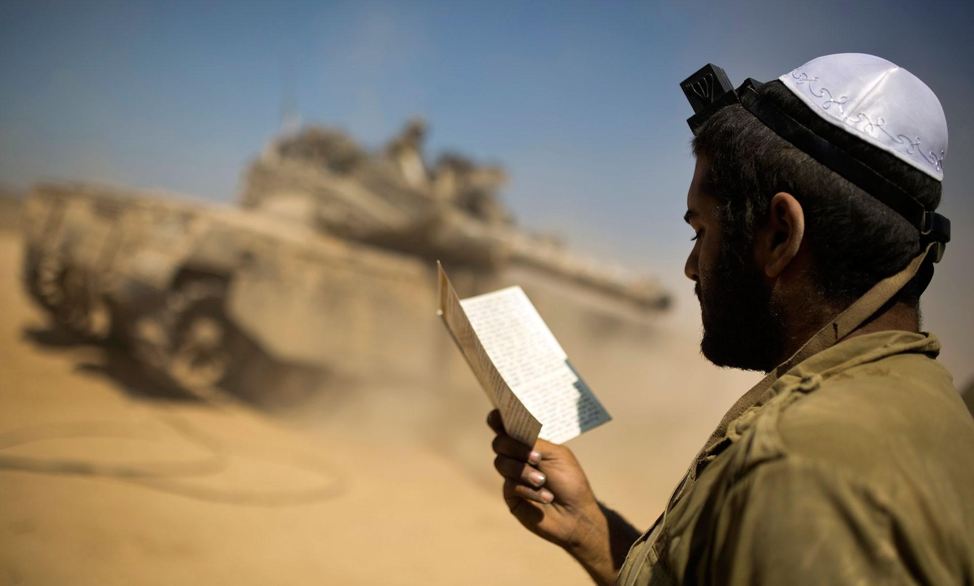 جندي إسرائيلي يؤدّي الصلاة (رويترز)