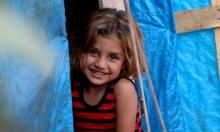 بسمة طفلة سورية في مخيم للاجئين