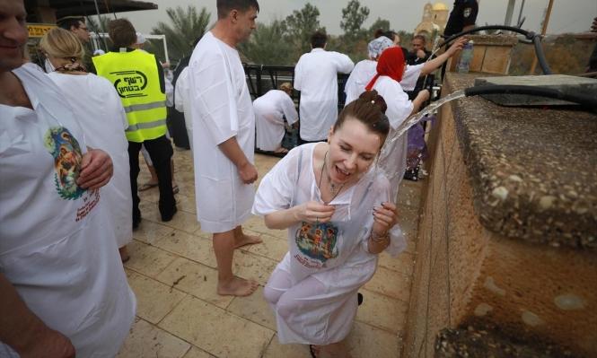 الآلاف من الفلسطينيين والأجانب يتعمدون في نهر الأردن