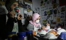 فلسطينيان يشجعان على استخدام الكمّامات الواقية من كورونا بتلوينها