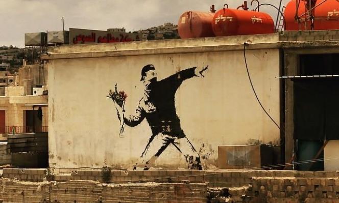 """""""الملثم الذي يرمي الزهور"""": بانكسي يخسر ملكيته لأحدى أشهر رسوماته!"""