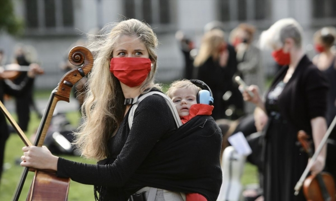 سيدة بريطانية وطفلها خلال تظاهرة لموسيقيين احتجاجا على قيود الوقاية من كورونا