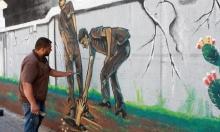 فنان غزّيٌ يرسم جدارية لأسرى نفق الحرية