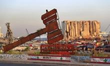 مجسّم ضخم مقابل آثار الدمار الذي خلفه انفجار مرفأ بيروت للمطالبة بالعدالة للضحايا